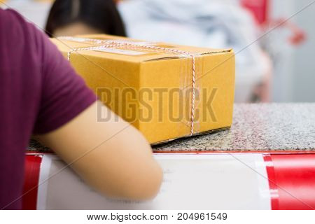 Girl took parcel or paper box to the post office. parcel or paper box on work desk prepared and ready for delivery .Woman working in post office