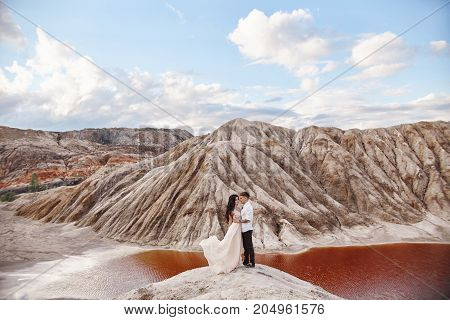Couple Stands On The Precipice Of The Mountain And The Red Lake And Hugging. The Bride And Groom In