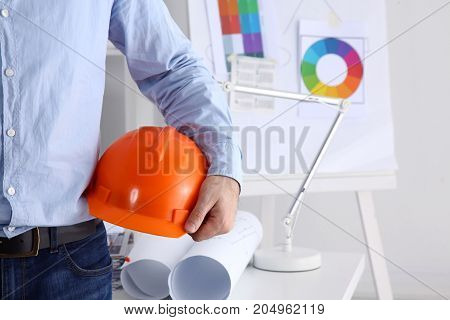 Man architect wearing suit holding helmet, standing in office.
