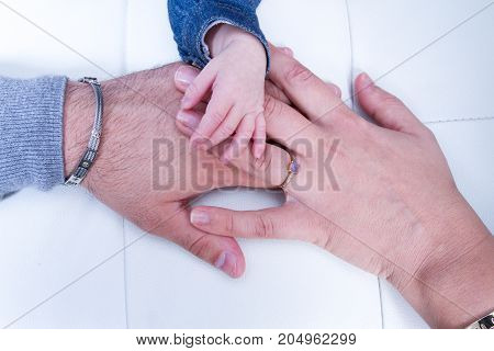 Father Mother And Baby Holding Hands Family