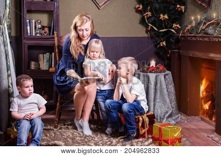 Studio shot of mother and three children spending time at reading during Christmas holidays