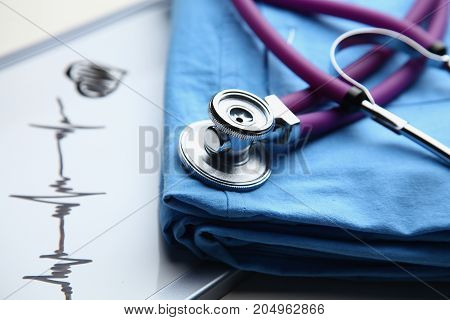 Doctor coat with medical stethoscope on the desk .