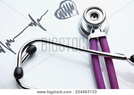 Medical stethoscope on a cardiogram on the desk.