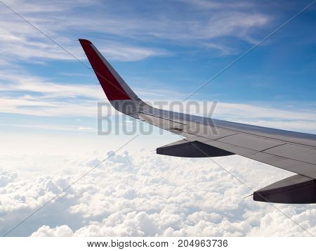 View of plane wing flight flying in sky among white cloud tourism operators and travel concept.