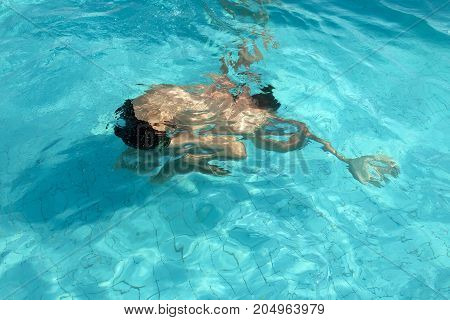 Ducked man in the pool with a strong distorting effect