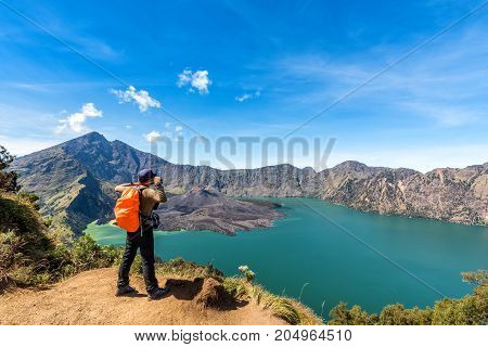Hiker man with orange backpack standing enjoy and happy with active volcano Baru Jari Lake Segara Anak and summit of Rinjani mountain view after finished climbing at Rinjani mountain Lombok Indonesia.