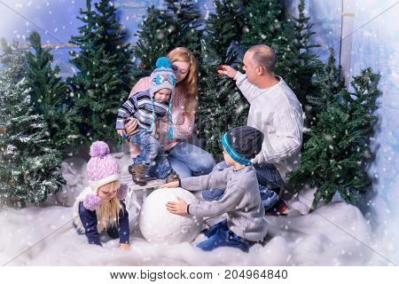 Studio shot of family, consisting of parents and three kids, playing with snow ball at winter time
