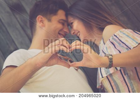 Romantic couple is making heart looking at each other and smiling