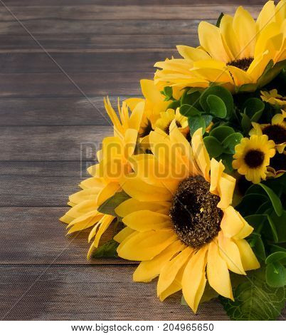 Closeup of a sunflower bouquet on dark brown wooden background with lots of copy space.