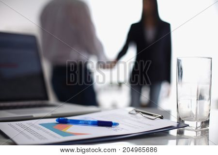 Laptop  computer with folder on the desk , two  businesspeople standing in the background.