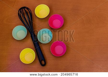 Cupcake silicon baking cups and whisk over wooden background with copy space