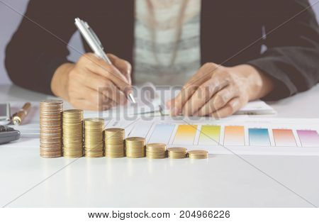 Businessman writing and analyzing for business with stack coins on the table. Financial analyzing and success concept.