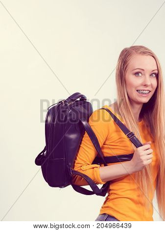 Happy young blonde teenage girl going to school or college wearing backpack.