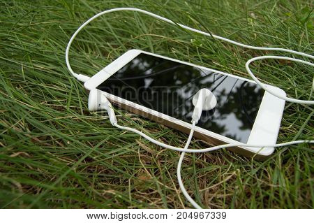 Smartphone and headphones lying on a background of green grass, break.