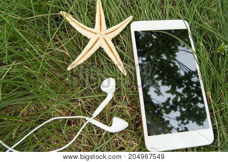 Plan your beach holidays and travel on the grass with the phone, headphones, starfish.