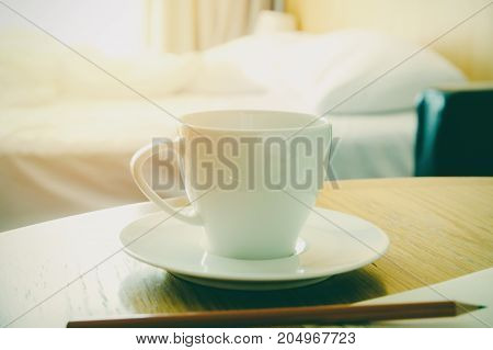 Hot cup of coffee on wooden table in bedroom fresh morning concept.