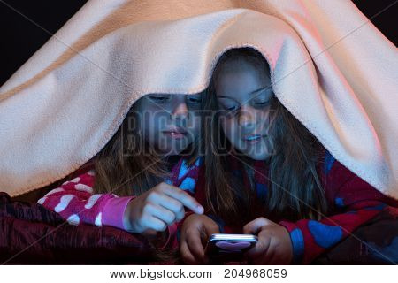 Pyjamas Party For Children: Girls Under Blanket Playing With Phone