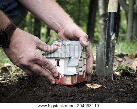 Male hands planting into the ground a little house. The concept of mortgage lending home insurance income from real estate