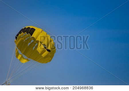 Black and yellow parachute on a blue sky background