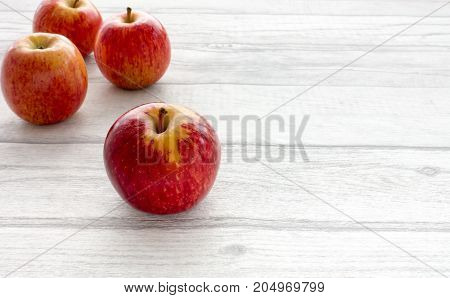 Closeup of four whole red apples on grey wooden background with copy space. Backlit.
