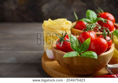 Fresh red cherry tomatoes with raw pasta, basil, chili pepper and garlic for Italian food, selective focus, copy space.