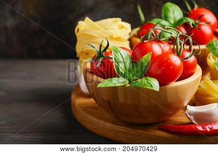 Fresh red cherry tomatoes with raw pasta, basil, chili pepper and garlic for Italian food, selective focus.