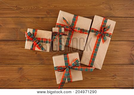 Gift boxes in craft paper decorated with checkered ribbon on wooden background. Presents for christmas, valentine day or birthday, top view, copy space