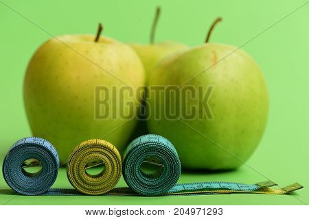 Apples Near Measuring Tape Rolls On Green Background, Close Up