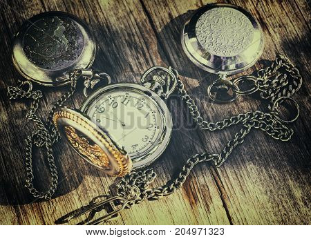 old pocket watch on an old wooden surface retro