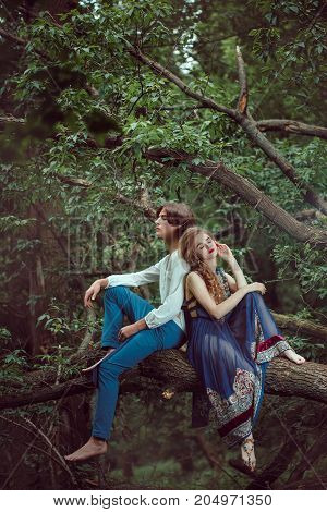 Young couple of elves in love siting on branch in magical forest outdoor on nature. Fairy tale love, relationship and magik people concept.