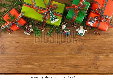 Colorful gift boxes, christmas ornaments and fir tree twigs, top view, copy space on wood background. Border of colored packages with checkered ribbon bows for christmas, valentine day or birthday
