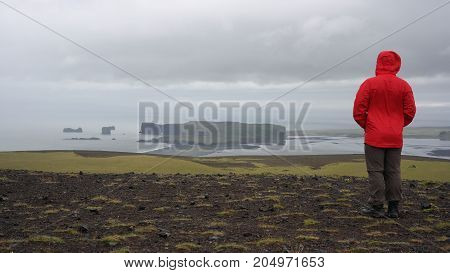 A man looking to Dyrholeay cape from a top of Reynisfjall mountain, Vík village, Iceland