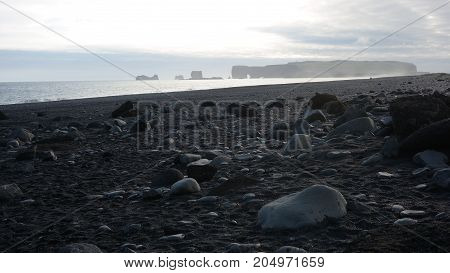 View of Dýrholaey cape from Reynisfjara black sand beach in Iceland