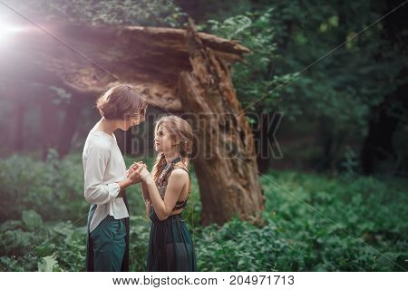 Young couple of elves in love in magical forest agaist the broken tree outdoor on nature. Fairy tale about love, relationship and magik people. Man holding woman by hands
