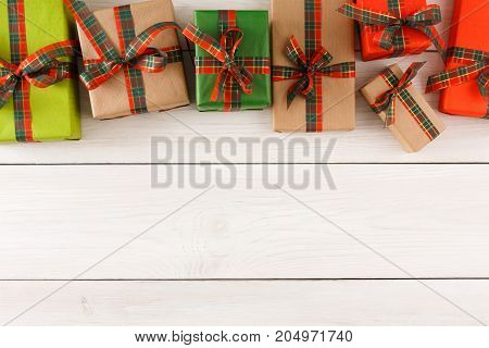 Gift boxes in craft and colorful wrapping paper decorated with satin ribbon bows border on wooden background. Presents for christmas, valentine day or birthday, top view, copy space