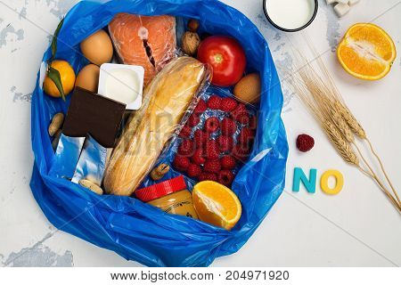 Good food in trash bag. Allergy food that's not allowed to eat. Overconsumption concept