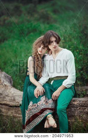 Young couple of elves in love siting on tree in magical forest outdoor on nature. Fairy tale love, relationship and magik people concept. Man and woman ambracing and looking down