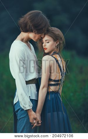 Young couple of elves in love standing in magical forest outdoor on nature. Fairy tale love, relationship and magik people concept. Man holding woman by hands