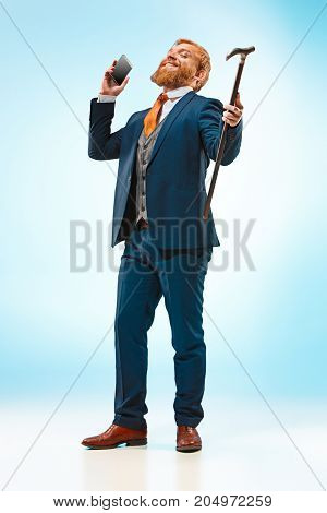 The bearded man in a suit holding cane and mobile phone. Isolated on a blue background.