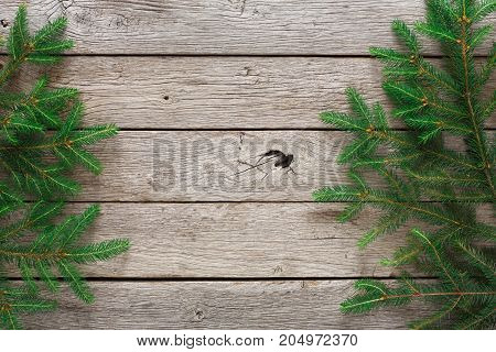 Christmas border background. Green fluffy pine tree twigs on aged wooden table. Winter holidays concept, top view, copy space