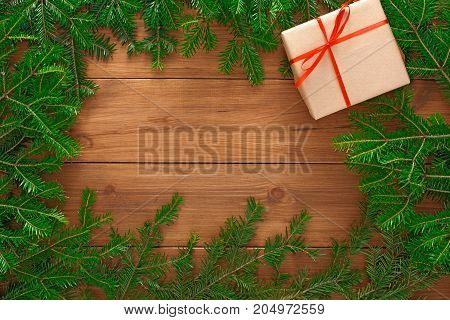 Christmas background. Present box in craft paper bounded with red satin ribbon and frame of green pine tree branches on wooden table. Handmade leisure and winter holidays concept