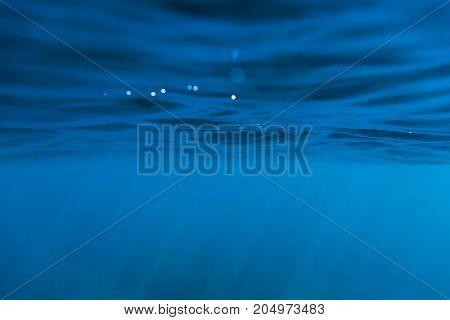 Waves underwater and sun rays. Blue ocean in underwater