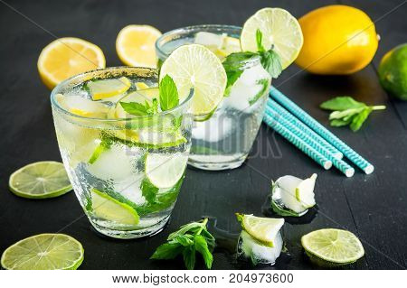 Refreshing fresh cocktail with crushed ice and lime with lemon on dark background