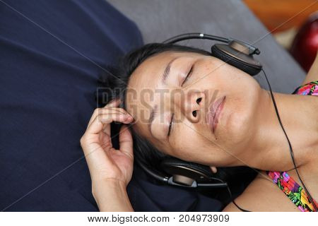 relaxed asian woman enjoying listening the music with headphones close eyes sleeping on summer