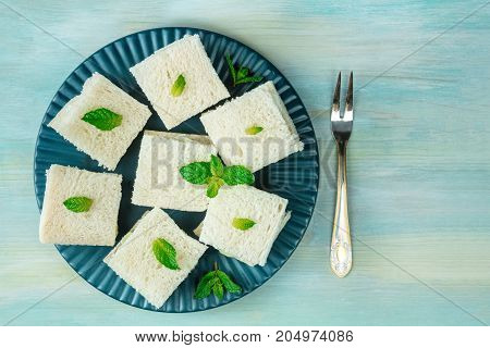 An overhead photo of a plate of cucumber sandwiches, shot from above on a teal blue texture with a place for text and a little vintage fork