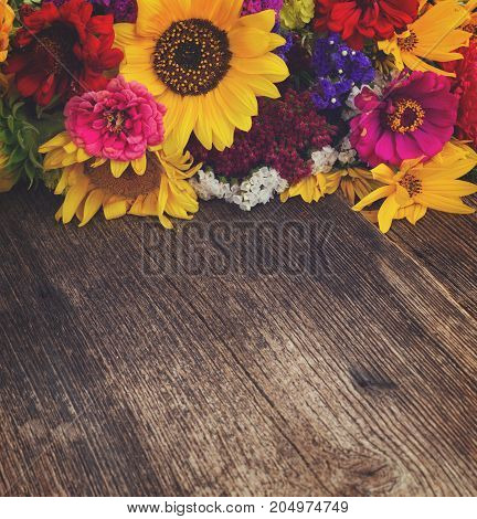 Bright bouquet with fresh fall flowers on wooden table with copy space, retro toned