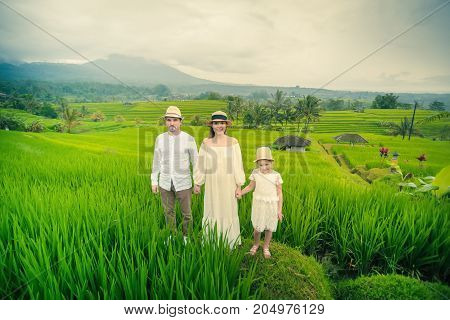 Happy family travelers taking selfie at mobile phone. People traveling in jatiluwih rice terrace, Bali, Indonesia.