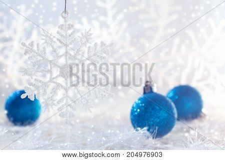 Christmas blue balls on white background with snowflakes. Selective focus.