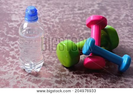 Dumbbells Made Of Plastic Near Water Bottle On Burgundy Background