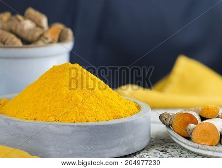 selective focus shot of powdered turmeric in a pile place in a light blue ceramic dish with raw root a dark background copy space at header and side